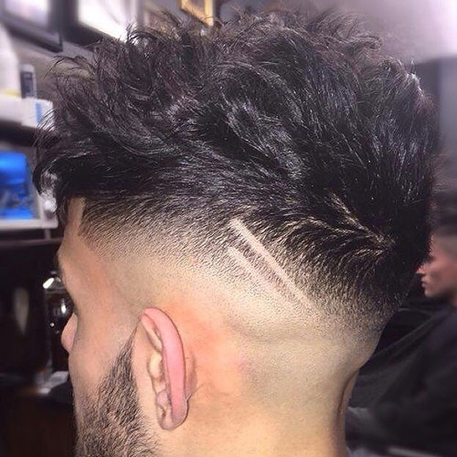 Messy textured hair with high razor fade and design